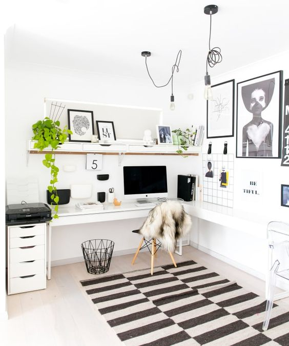 a Scandinavian home office with a corner desk, a couple of chairs, a shelf with drawers, a gallery wall and a printed rug