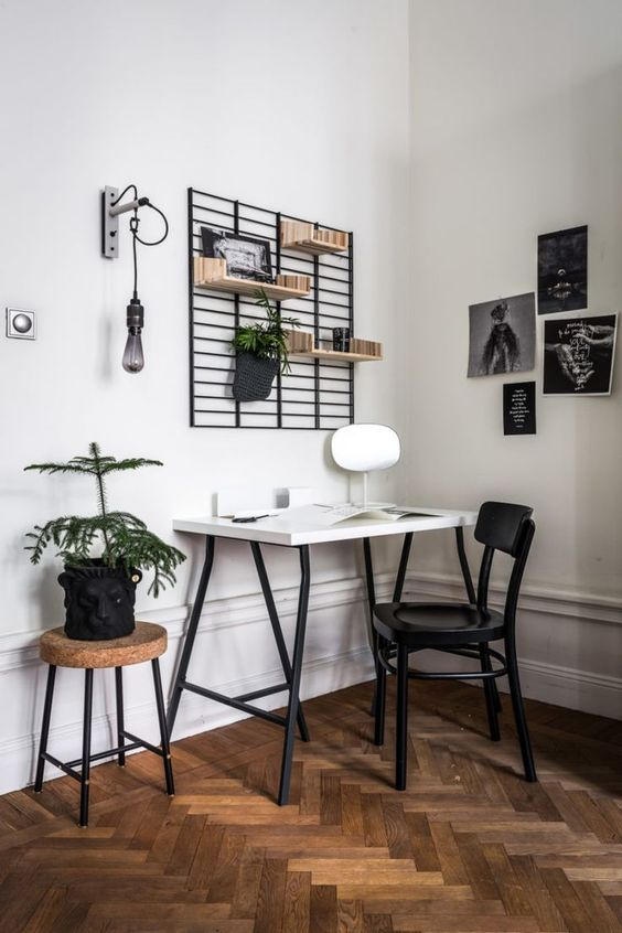 a Scandinavian home office with a white desk, a black chair, a cork stool, a grid with shelves, a black and white gallery wall