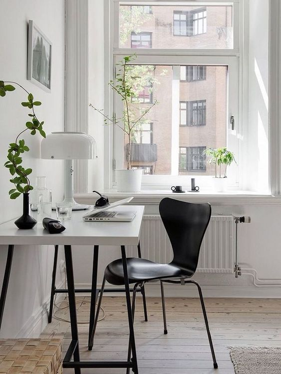 a Scandinavian home office with a white desk, a black chair, potted plants and a white table lamp is very chic