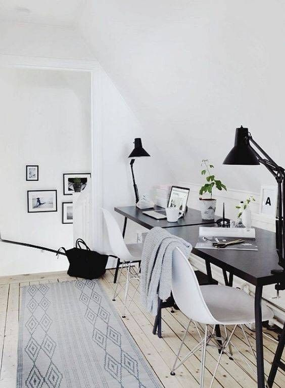 a Scandinavian home office with two black desks, white chairs, black table lamps and a gallery wall is stylish and simple