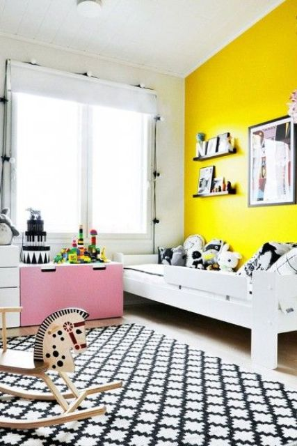 a Scandinavian kid's room with a neon yellow accent wall, white furniture, a pink cabinet, lots of prints and lights over the window