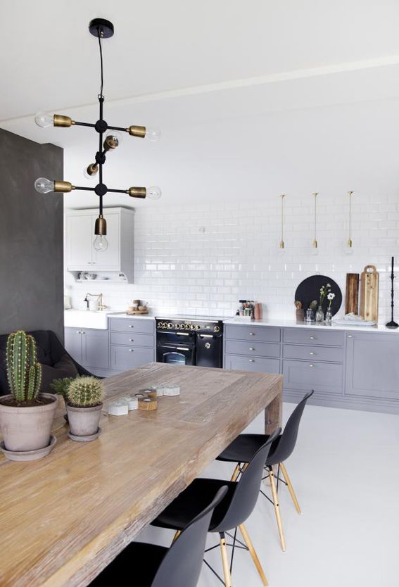 a Scandinavian kitchen with grey and white cabinets, white subway tiles, a wooden table and black chairs is very fresh