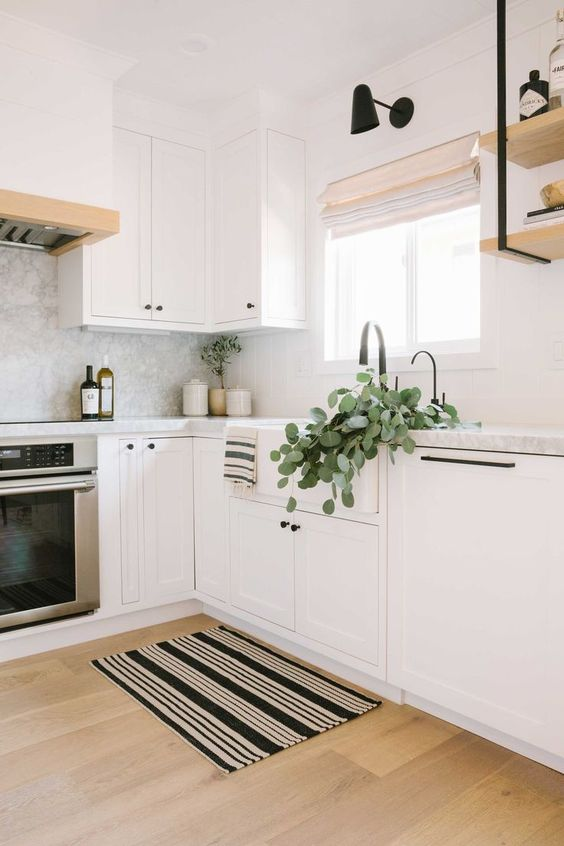 a beautiful Scandinavian L-shaped kitchen in white, with a grey marble backsplash, black touches and a striped rug