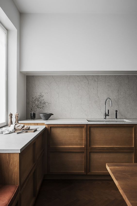 a beautiful Scandinavian kitchen with lower wooden cabinets and white stone countertops plus a marble backsplash