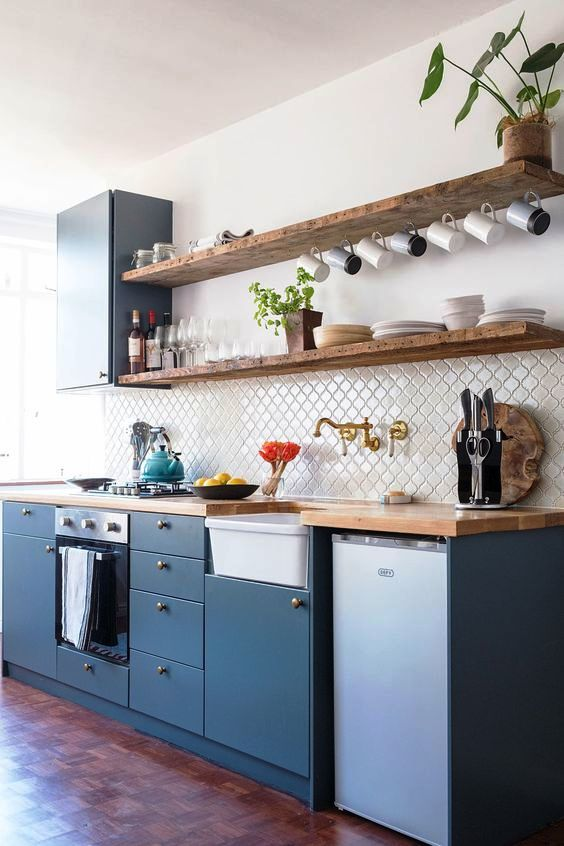a beautiful blue one wall kitchen with a white Moroccan tile backsplash and butcherblock countertops, open shelves and potted plants