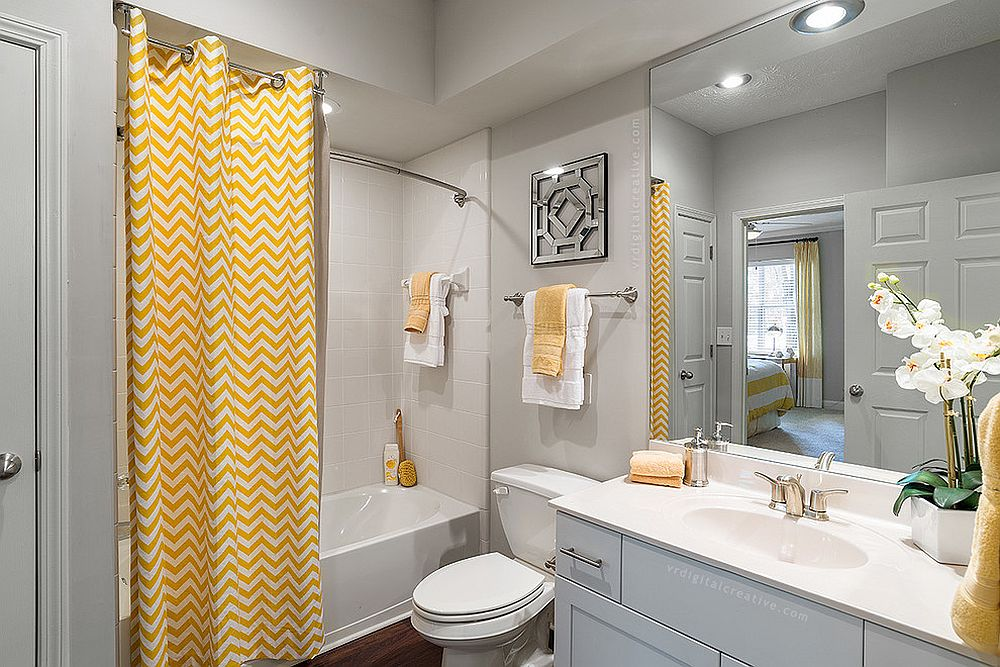 a beautiful light grye bathroom with white furniture and appliances, with yellow chevron curtains and some towels