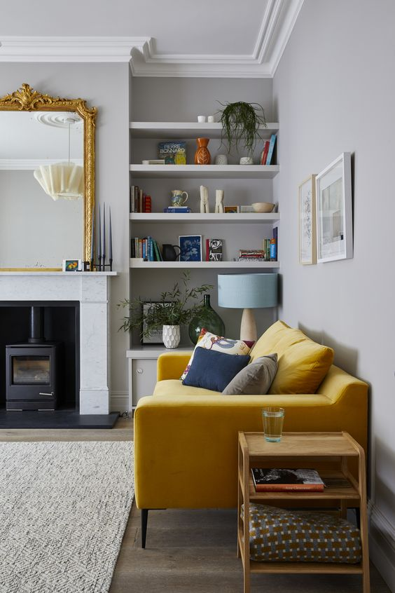 a beautiful modern living room with dove grey walls, a hearth, a mirror in a gold frame, a yellow sofa, niches with shelves for displays