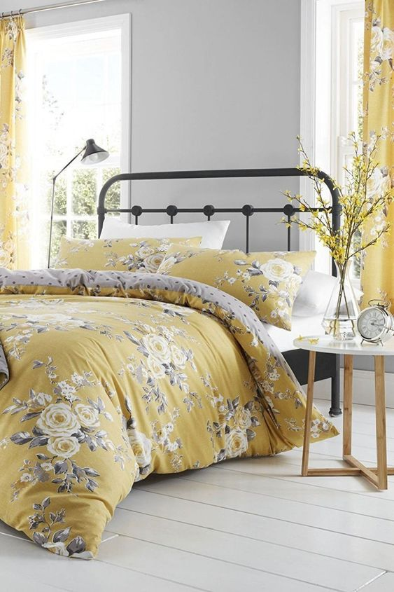 a bedroom with grey walls, a metal bed, bright mustard floral textiles, a nightstand with yellow blooms in a vase