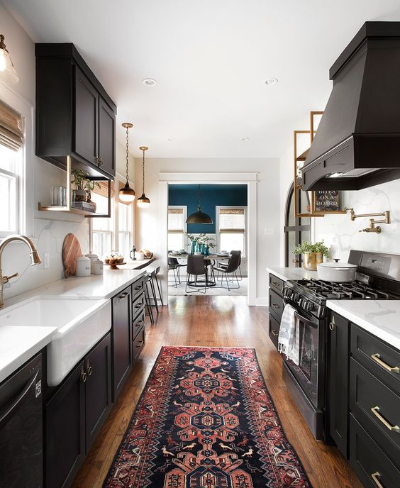 a black galley kitchen with white stone countertops and elegant brass touches here and there