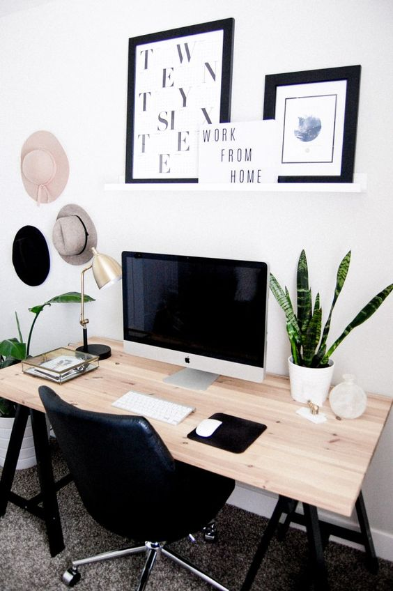a boho Nordic home office with a trestle desk, a black chair, potted plants, black and white artworks, hats on the wall is very cozy