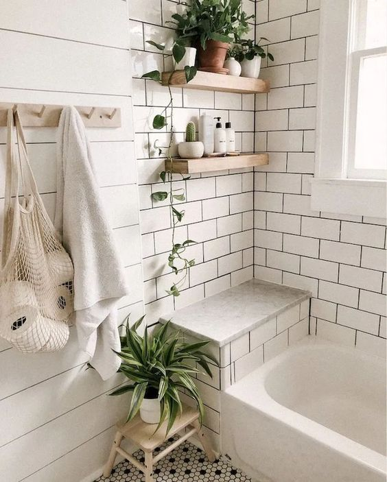 a boho Scandi bathroom with two types of tiles - subway and penny ones, beadboards, wooden furniture and greenery