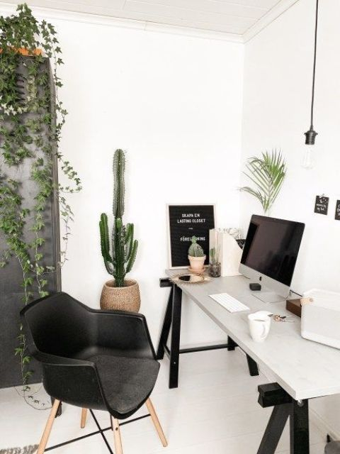 a boho Scandinavian home office with a trestle desk, a black chair, potted plants and artworks plus pendant bulbs