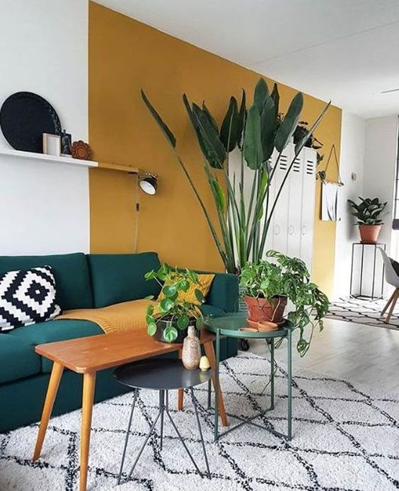 a boho living room with a mustard color block wall, dark furniture, potted plants, graphic prints and pillows is cool