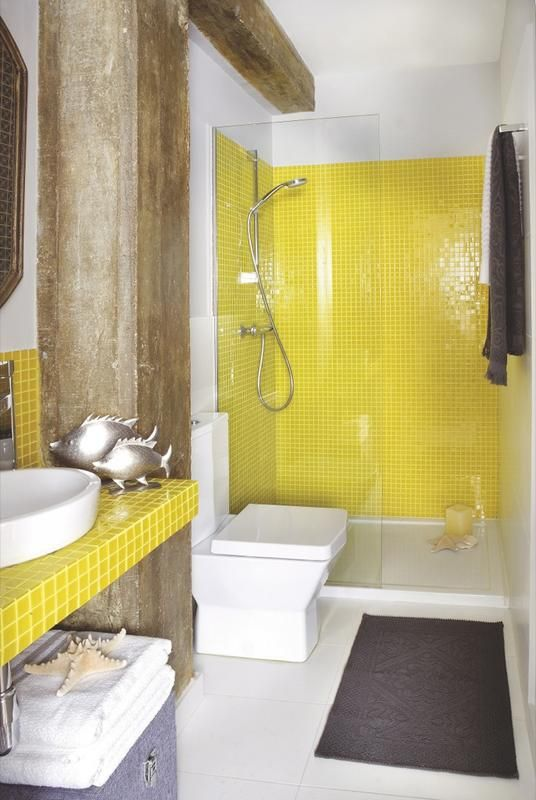 a bold bathroom with white walls, lemon yellow tiles, rough wooden beams, grey upholstery and textiles