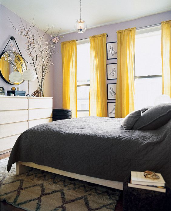 a bold bedroom with lavender walls, white furniture, bright yellow curtains, grey and white bedding