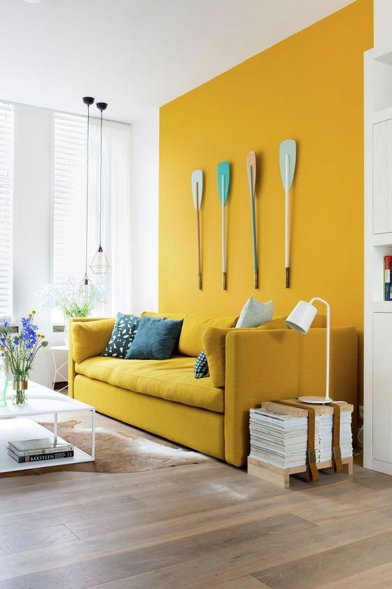 a bold contemporary living room with a sunny yellow wall and a matching sofa, oars on the wall, some simple white furniture and decor