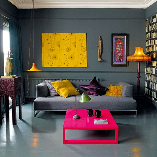 a bold living room with graphite grey walls, a floor and a sofa, bold yellow touches and a hot pink coffee table