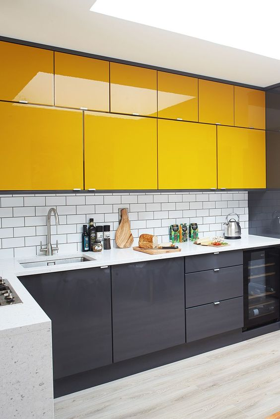 a bold minimal kitchen with lower graphite grey cabinets and bold yellow upper ones plus a white subway tile backsplash