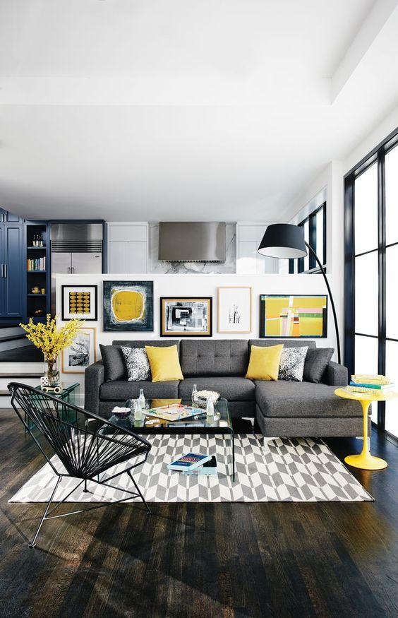 a bold modern living room with a grey sectional, a printed rug, a bright gallery wall, a black floor lamp and a yellow table