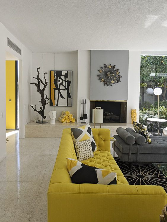 a bold neutral, grey and yellow living room with a built-in fireplace, refined furniture, printed textiles and uellow touches here and there