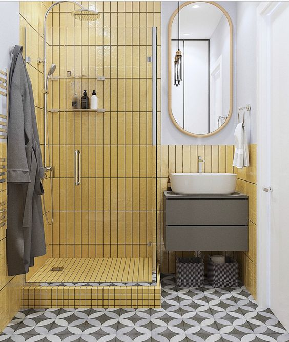 a bold yellow bathroom with a grey tiled floor, grey furniture and a mirror in a yellow frame is super cool