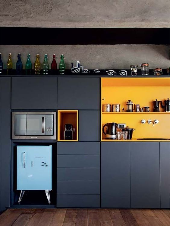 a bright and cool contemporary kitchen done in graphite grey with with bold yellow niches plus a blue fridge