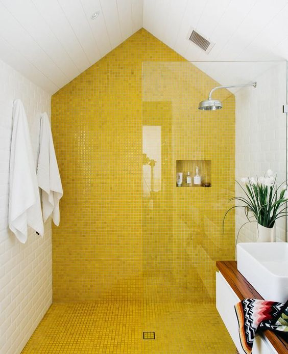 a bright bathroom with a yellow tile wall and floor in the shower to accent this zone and make it stand out in the space