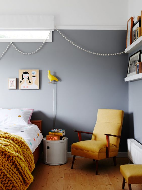 a bright bedroom with grey walls, elegant mid-century modern furniture, a mustard chunky blanket, a yellow bird lamp and bright art