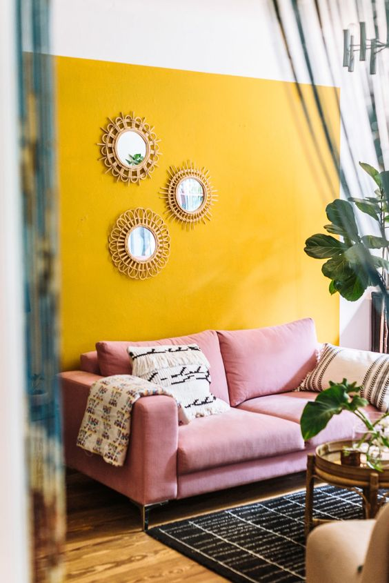 a bright boho living room with a yellow accent wall, a pink sofa, a printed rug, some potted plants and an arrangement of mirrors