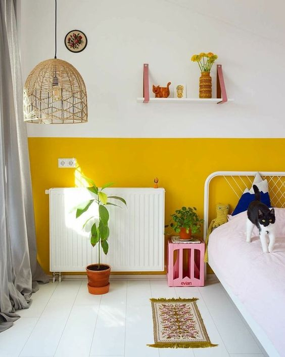 a bright kid's space with a color block accent wall, white and pink furniture, a wicker pendant lamp and some potted plants
