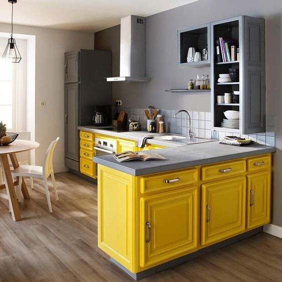a bright kitchen with bold yellow lower cabients and grey upper ones, a white tile backsplash and stainless steel appliances