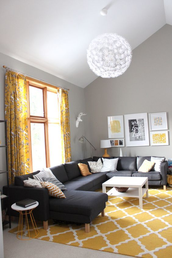 a bright living room with grey walls, a black sectional, a mustard rug and floral curtains plus a gallery wall