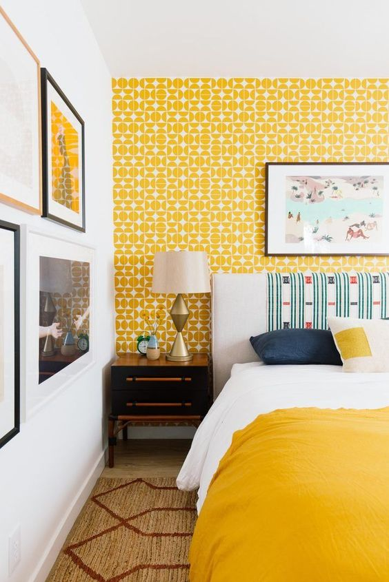 a bright mid-century modern bedroom with a yellow wallpaper wall, bright bedding, vintage nightstands, a gallery wall with pretty artworks