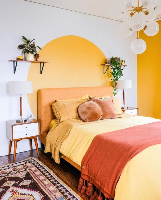a bright mid-century modern bedroom with an accent yellow wall and a color block one, a rust bed with colorful bedding, a boho rug and potted plants
