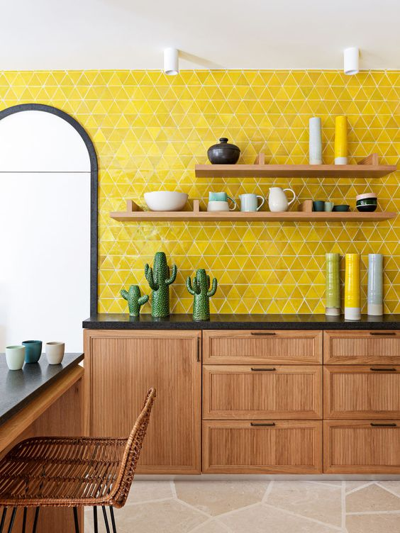 a bright mid-century modern kitchen with a bold yellow tile wall, wooden furniture, black countertops, wicker chairs and funny tableware