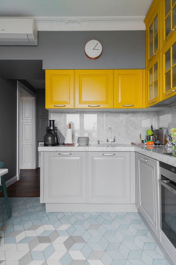 a bright modern kitchen with grey and yellow cabinetry, grey marble coutnertops and a backsplash plus stainless steel appliances