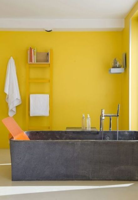a bright yellow bathroom with a concrete tub, a yellow ladder, shelves and neutral textiles is very modern and bold