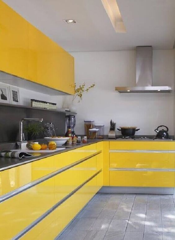 a bright yellow kitchen with a grey backsplash and countertops, stainless steel appliances and some bold blooms