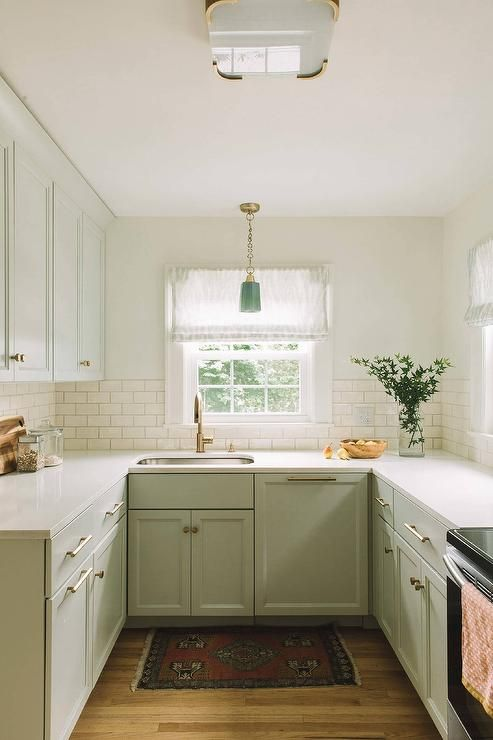 a calm light green kitchen with white subway tiles, a green pendant lamp, a boho rug and metallic touches