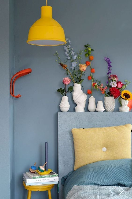 a catchy bedroom in grey, with a textural headboard, grey and yellow bedding, a pendant yellow lamp and stool and bold blooms