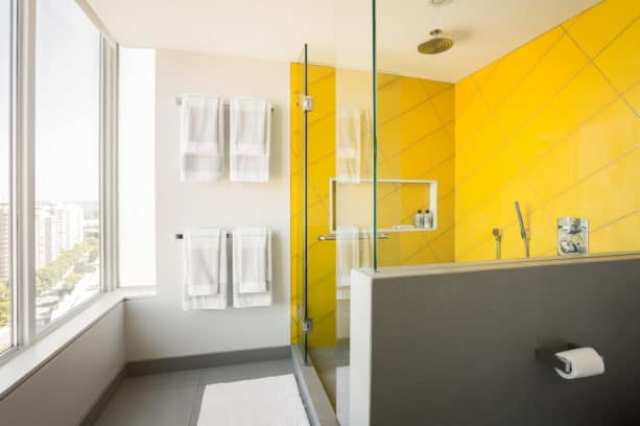 a catchy modern bathroom with a bold yellow and grey shower zone and a window for much light and cool views