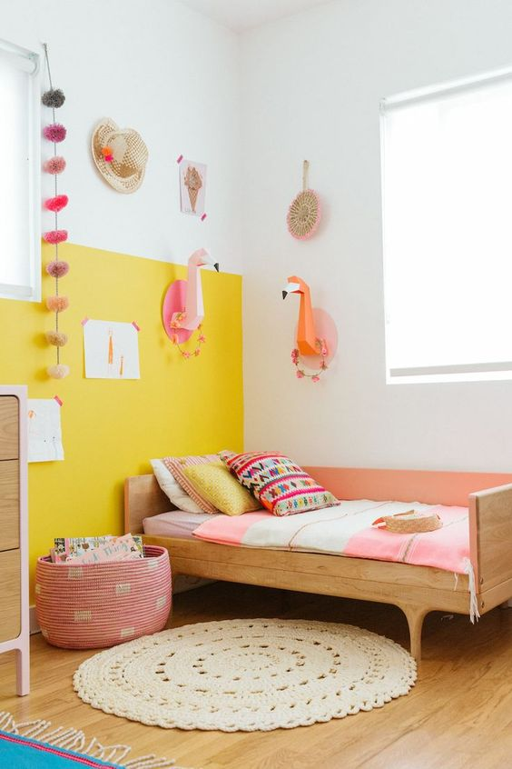 a cheerful kid's room with a color block yellow wall, simple wooden furniture, paper taxidermy and colorful touches