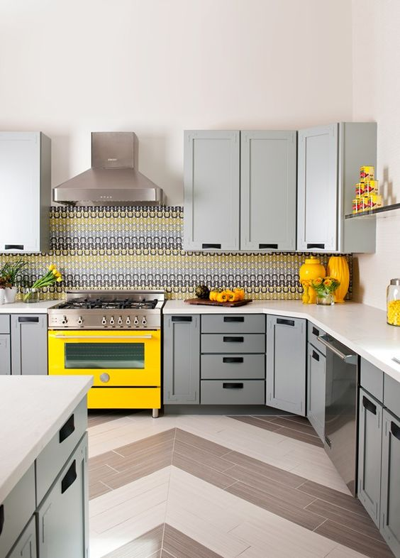 a cheerful modern ktichen with light grey cabinetry, a bold yellow cooker, chevron tile floor and a colorful tile backsplash