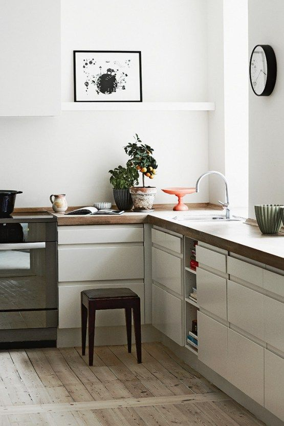a chic L-shaped Scandinavian kitchen in white, with butcherblock countertops, open shelves and potted plants