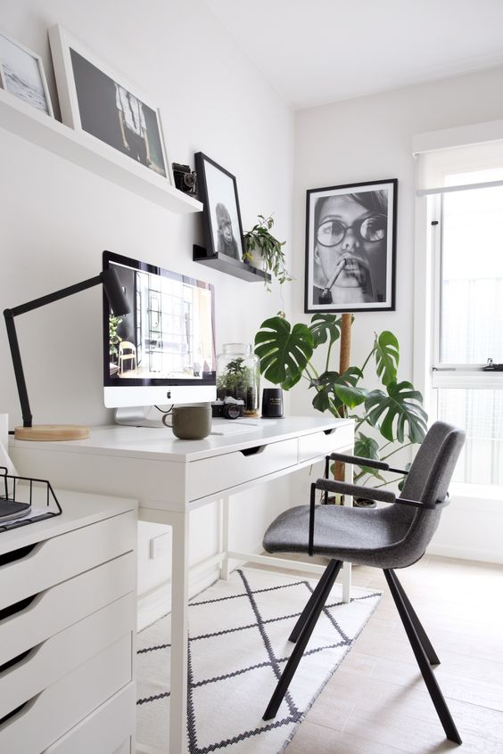 a chic Nordic home office with a white desk and a cabinet, a grey chair, shelves with artworks and some potted plants