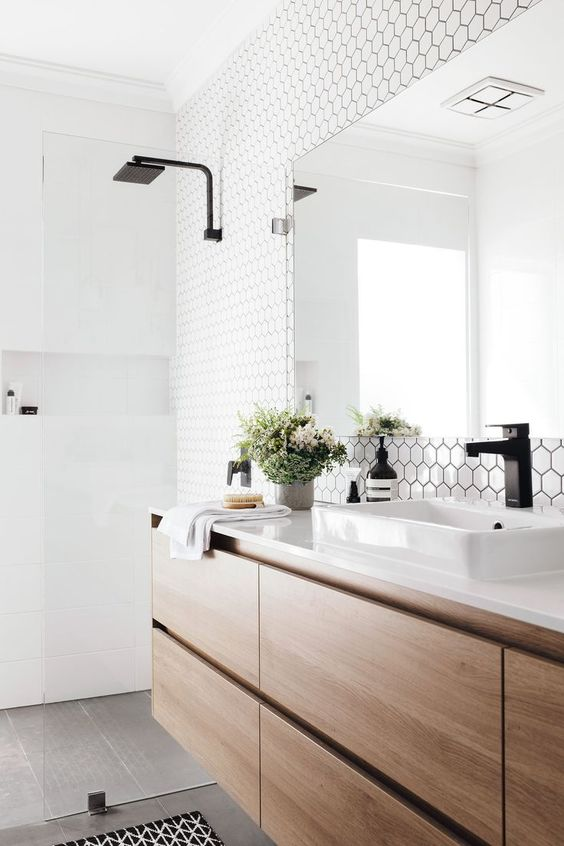 a chic Scandinavian bathroom with white hex and square tiles, a floating wooden vanity and black touches here and there