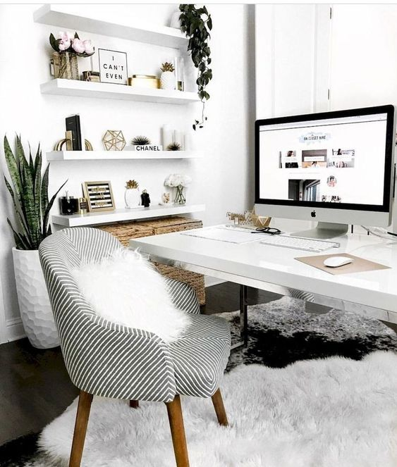 a chic Scandinavian home office with white floating shelves, a white desk, a grey chair, potted plants and fluffy rugs is welcoming