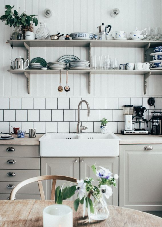 a chic Scandinavian kitchen with grey cabinetry and shelves, beadboard and white tiles feels vintage and refined