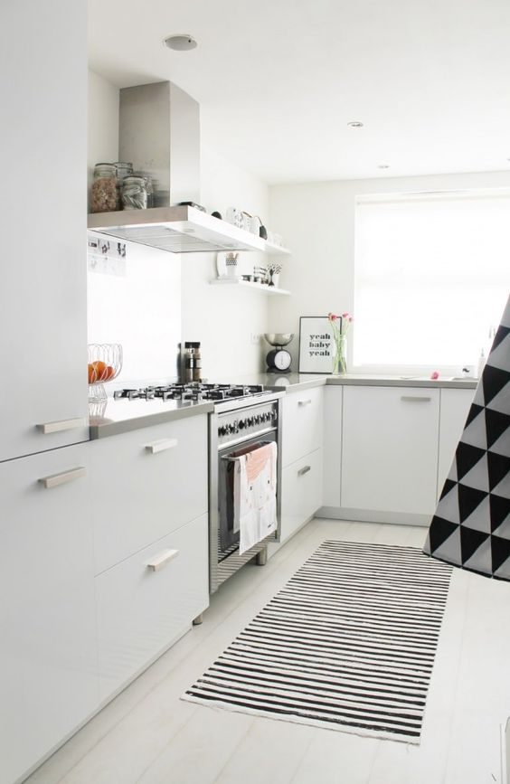 a chic Scandinavian kitchen with plain white cabinets, stone countertops, printed linens and stainless steel