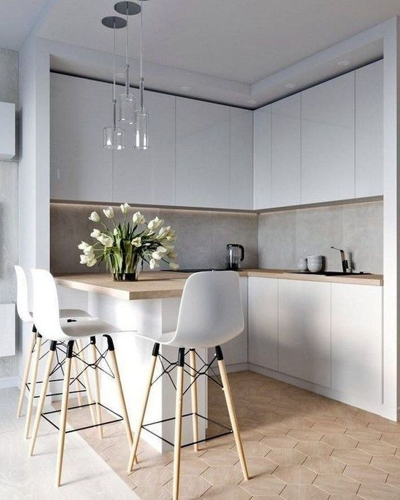 a chic airy Nordic kitchen with sleek white cabinetry, wooden countertops, grey tiles and a breakfast bar with lights